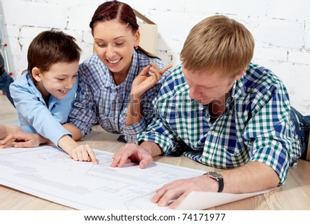 Young family discussing plan of new apartment - stock photo