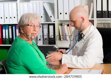 young family doctor examine a female senior - stock photo