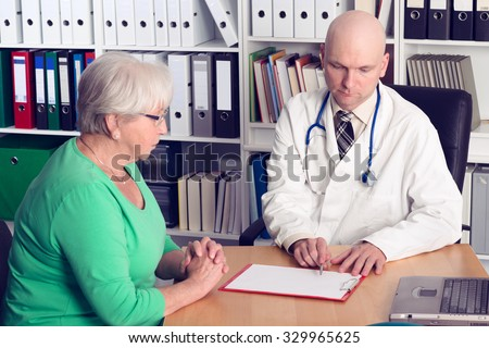 young family doctor in interview with a female senior - stock photo