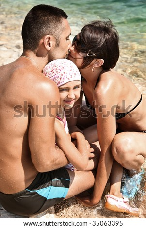 Young family embracing on a sandy beach - stock photo