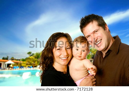 Young family enjoying a sunny holiday with a young baby. - stock photo