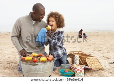 Young Family Enjoying Barbeque On Beach - stock photo