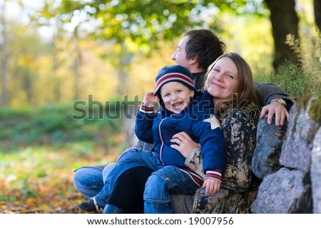 Young family enjoying beautiful autumn day - stock photo
