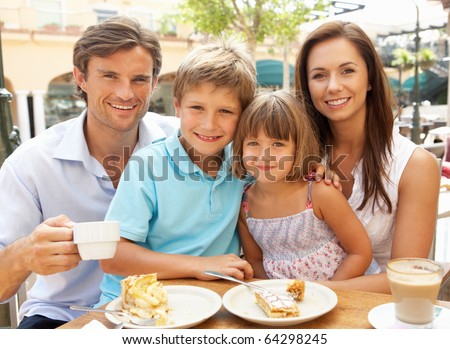 Young Family Enjoying Cup Of Coffee And Cake In Cafe Together - stock photo