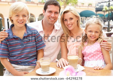 Young Family Enjoying Cup Of Coffee In Cafe Together - stock photo
