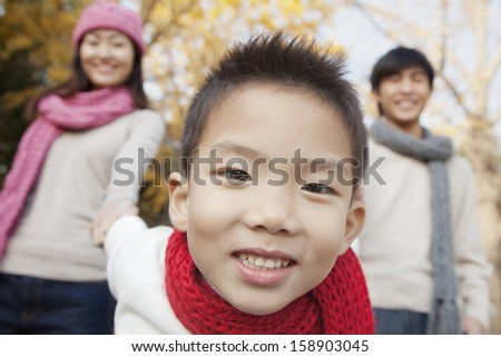 Young family enjoying park in autumn