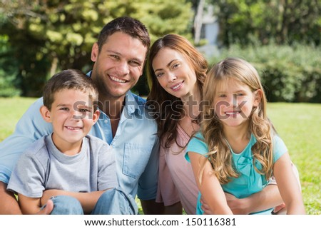Young family enjoying the sun in a park smiling at camera