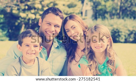 Young family enjoying the sun in a park smiling at camera - stock photo