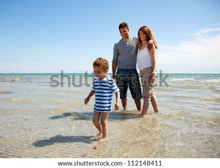 Young family enjoying the weekend on a sunny beach - stock photo