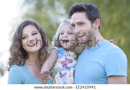 young family, father mother and daughter in park setting - stock photo