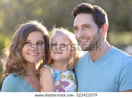 young family, father mother and daughter in park setting