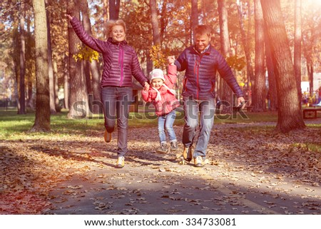 Young Family Father Mother and Little Child in Autumnal Forest Running Holding Hands - stock photo