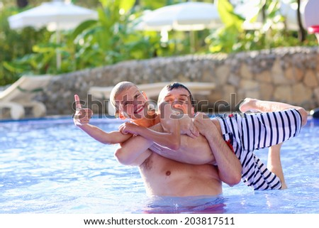 Young family, father with child, happy teenage boy, having fun together playing in swimming pool in outdoors aquapark during summer sea vacation in tropical resort - stock photo