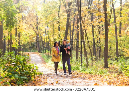 Young family for a walk in a autumn park with baby - stock photo