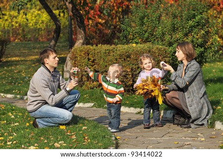 Young family for a walk in the autumn park with two children bubbles - stock photo