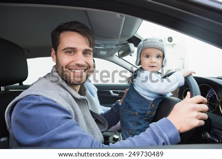 Young family going for a drive in their car - stock photo