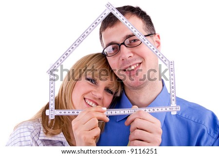 young family granting a loan for new house - building new home metaphoricaly, isolated on white background - stock photo