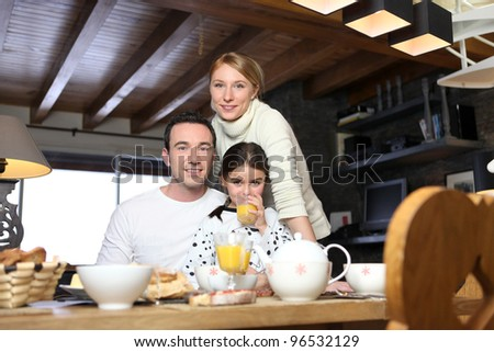 Young family having breakfast - stock photo