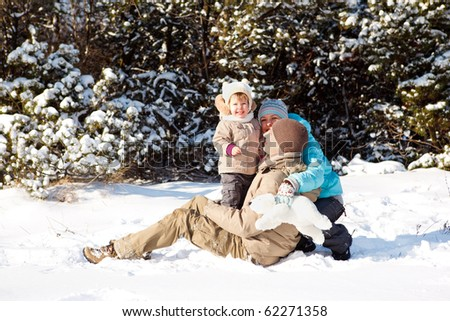 Young family having fun in snow - stock photo