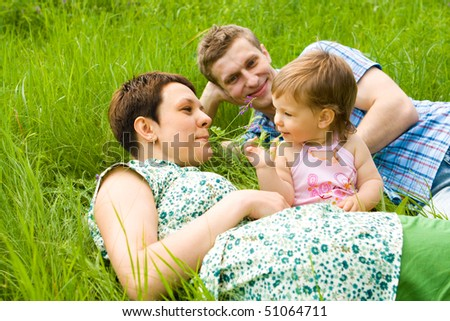 Young family having fun  in the spring grass - stock photo