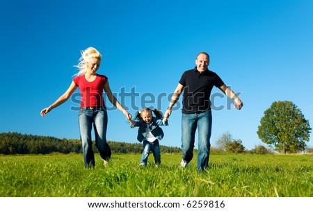 Young family having fun in the sun running - stock photo