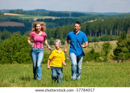 Young family having fun in the sun running over the meadow an a bright summer day - stock photo