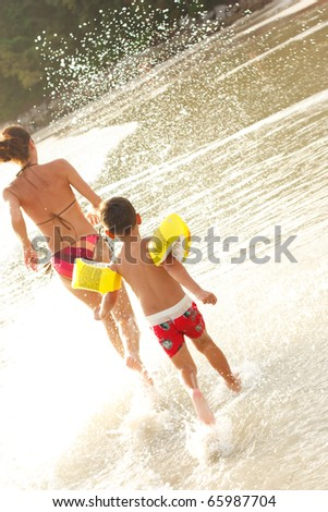 Young family having fun on beach - stock photo