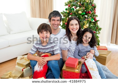 Young family having fun with Christmas presents - stock photo