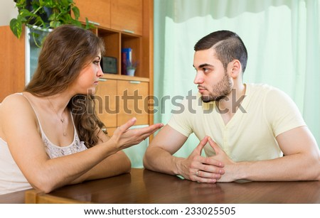 Young family having serious talking at the table in home - stock photo