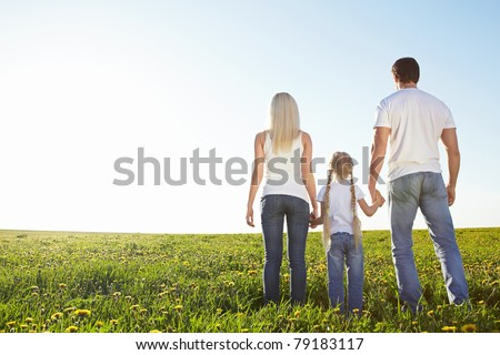Young family in a field - stock photo