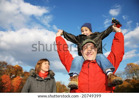 Young family in autumn park. Father holding his son on his shoulders against blue sky. - stock photo