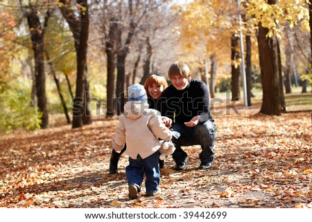 Young family in autumn park. Outdoors - stock photo