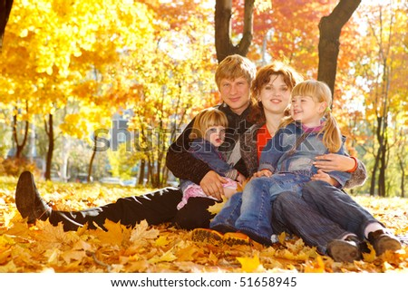 Young family in autumn park sitting  on yellow leaves - stock photo