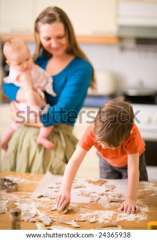 Young family in kitchen making gingerbread cookies. - stock photo