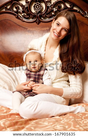 Young family in the bedroom. Mother and daughter in the interior. Mom and baby are playing together. - stock photo