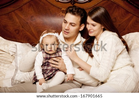Young family in the bedroom. Mother, father and daughter in the interior. Mom, dad and baby are playing together.