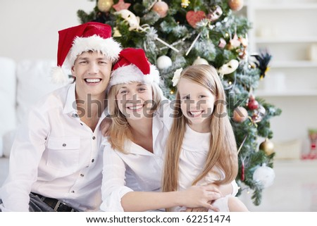 Young family in the cap on the background of trees - stock photo