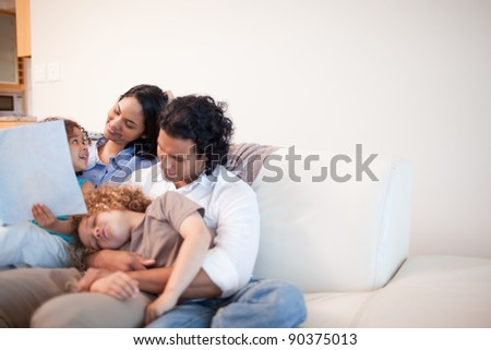 Young family in the living room looking at photo album together - stock photo