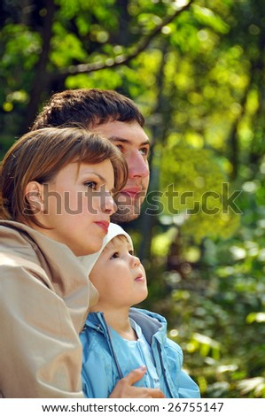 young family in the park looking far away