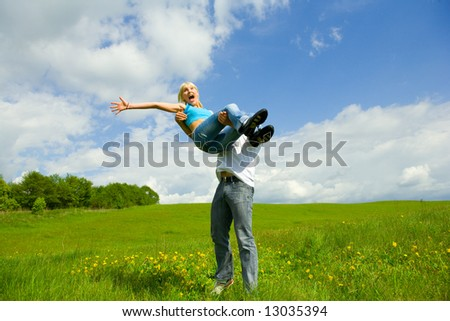 Young family jumping on a lawn