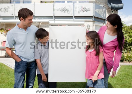 Young family looking at a empty sign board outside their house - stock photo