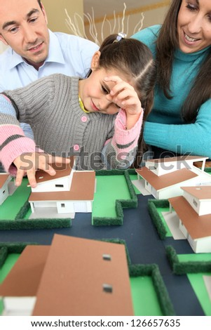 Young family looking at model house - stock photo