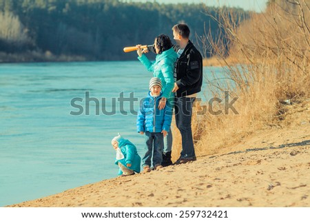 young family looks into the distance through a spyglass - stock photo