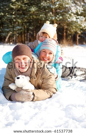 Young family lying in a winter park - stock photo