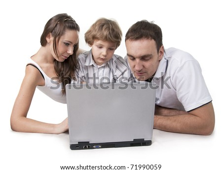 Young family lying on a floor with the computer on white isolation