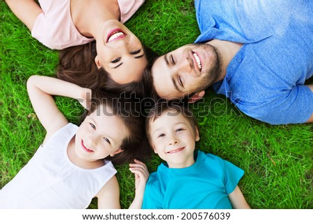 Young family lying on grass - stock photo