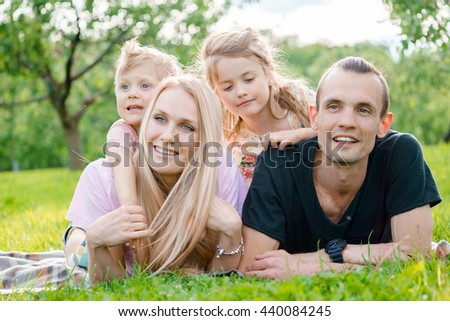 Young family lying on grass in countryside