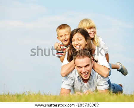 Young family lying on green summer grass meadow having happy life - stock photo