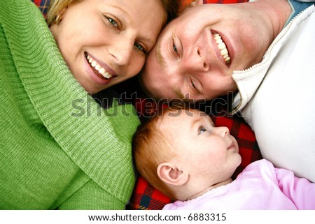 Young family lying on picnic rug , enjoying the outdoors. - stock photo