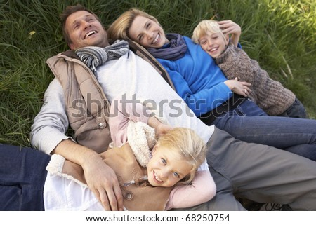 Young family lying together on grass - stock photo